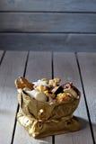Διάφορα μπισκότα Χριστουγέννων στο χρυσό sacket στο ξύλινο υπόβαθρο στοκ εικόνες