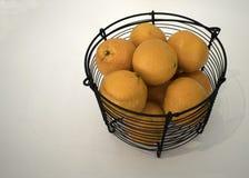 Διάφορα πορτοκάλια γεμίζουν ένα μαύρο καλάθι μετάλλων στην άσπρη επιφάνεια Στοκ φωτογραφία με δικαίωμα ελεύθερης χρήσης
