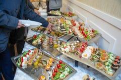 Διάφορα πρόχειρα φαγητά επιτραπέζιων καθορισμένα υπηρεσιών τομέα εστιάσεως σε έναν πίνακα στο συμπόσιο Σύνολο κρύων πρόχειρων φαγ στοκ εικόνα