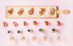 Διάφορα πρόχειρα φαγητά, σάντουιτς brushetta, πυροβολισμοί gazpacho, επιδόρπια πέρα από το ρόδινο υπόβαθρο Στοκ Φωτογραφία