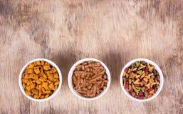 Διάφορα τρόφιμα γατών Διαφορετικοί τύποι τροφίμων γατών Κύπελλα με τα τρόφιμα γατών στο ξύλινο υπόβαθρο στοκ εικόνα με δικαίωμα ελεύθερης χρήσης