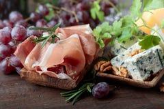 Διάφορα τυριά, σταφύλια και prosciutto στοκ εικόνες