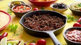 Διάφορα φρέσκα και νόστιμα συστατικά για τα τσίλι con carne Με το κρέας στο τηγάνι σιδήρου απόθεμα βίντεο