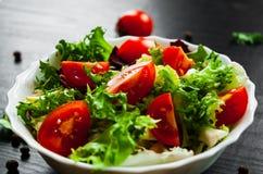 Διάφορα φρέσκα φύλλα σαλάτας μιγμάτων με την ντομάτα στο κύπελλο Στοκ Φωτογραφία