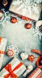 Διάφορα δώρα Χριστουγέννων με χειροποίητα snowflakes εγγράφου και κόκκινες εορταστικές διακοσμήσεις διακοπών στο ανοικτό μπλε εκλ Στοκ εικόνα με δικαίωμα ελεύθερης χρήσης