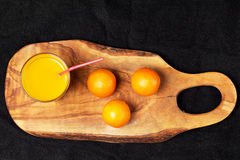 Διάφορα ώριμα εσπεριδοειδή και ένα ποτήρι του χυμού σε έναν ξύλινο πίνακα σε έναν πίνακα - μανταρίνια Στοκ φωτογραφία με δικαίωμα ελεύθερης χρήσης