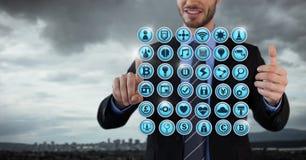 Διάφορα app εικονίδια που κωπηλατούνται και επιχειρηματίας με τα χέρια σχετικά με τον αέρα στο γραφείο πόλεων Στοκ φωτογραφία με δικαίωμα ελεύθερης χρήσης