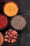 Διάφορα superfoods στο μικρό κύπελλο στο μαύρο υπόβαθρο στοκ εικόνα