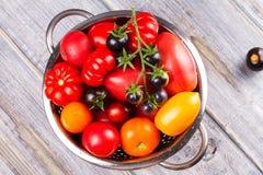 Διάφορες ζωηρόχρωμες ντομάτες Κόκκινες, κίτρινες, πορτοκαλιές και μαύρες ντομάτες στο ξύλινο υπόβαθρο Στοκ Εικόνες