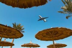 Διάφορες ομπρέλες παραλιών αχύρου και ένα αεροπλάνο στοκ φωτογραφία με δικαίωμα ελεύθερης χρήσης