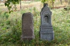 Διάφορες πολύ παλαιές ταφόπετρες, πλήρεις της λειχήνας και των εξασθενισμένων επιγραφών στη χλόη ενάντια στο σκούρο πράσινο φράκτ Στοκ Εικόνα