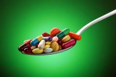 Διάφορες χάπια, κάψες και ταμπλέτες που συσσωρεύονται σε ένα κουτάλι Στοκ Εικόνες