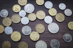 Διάφορη συλλογή νομισμάτων στον παλαιό ξύλινο πίνακα Στοκ Εικόνες