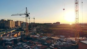 Διάφοροι ανυψωτικοί γερανοί στέκονται σε ένα εργοτάξιο οικοδομής επάνω από την όψη φιλμ μικρού μήκους