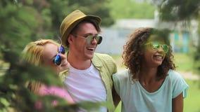 Διάφοροι στενοί φίλοι που αστειεύονται γύρω, που αγκαλιάζουν και που χορεύουν στο φεστιβάλ μουσικής απόθεμα βίντεο
