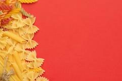 Διάφοροι τύποι άψητων ζυμαρικών σε μια πορτοκαλιά τοπ άποψη υποβάθρου τοποθετήστε το κείμενο στοκ εικόνες