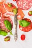 Διάφοροι τύποι ιταλικών λουκάνικων και ζαμπόν με το pesto και το μαχαίρι βασιλικού στοκ φωτογραφίες