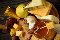 Διάφοροι τύποι τυριών σε έναν αγροτικό ξύλινο πίνακα στοκ εικόνα