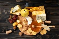 Διάφοροι τύποι τυριών σε έναν αγροτικό ξύλινο πίνακα στοκ φωτογραφίες