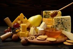 Διάφοροι τύποι τυριών σε έναν αγροτικό ξύλινο πίνακα στοκ φωτογραφία