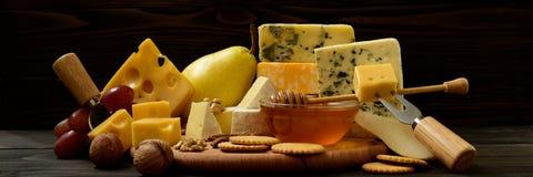 Διάφοροι τύποι τυριών σε έναν αγροτικό πίνακα στοκ φωτογραφία