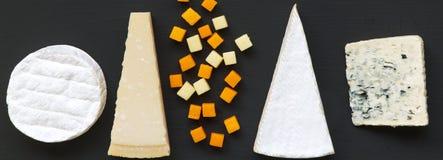 Διάφοροι τύποι τυριών στο μαύρο υπόβαθρο Τρόφιμα για το κρασί Επίπεδος βάλτε Από ανωτέρω στοκ εικόνες
