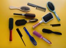 Διάφορος που χρωματίζεται brushs και χτένες για την τρίχα στο κίτρινο υπό στοκ φωτογραφίες
