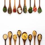 Διάφορος των ζυμαρικών και των συστατικών στο ξύλινο κουτάλι με την άσπρη πλάτη Στοκ Εικόνες