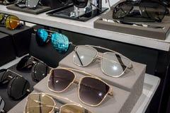Διάφορος των ζωηρόχρωμων γυαλιών ήλιων στα ράφια επίδειξης καταστημάτων Στοκ Φωτογραφία