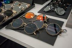 Διάφορος των μαύρων και χρυσών γυαλιών ήλιων στα ράφια επίδειξης καταστημάτων Στοκ φωτογραφία με δικαίωμα ελεύθερης χρήσης
