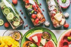 Διάφορο ζωηρόχρωμο εμποτισμένο νερό στα μπουκάλια με τα μούρα φρούτων, αγγούρι, χορτάρια με τα συστατικά στο επιτραπέζιο υπόβαθρο Στοκ Εικόνα