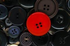 Διάφορο σκοτεινό υπόβαθρο κουμπιών ενδυμάτων με ένα κόκκινο κουμπί στοκ φωτογραφίες με δικαίωμα ελεύθερης χρήσης