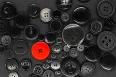 Διάφορο σκοτεινό υπόβαθρο κουμπιών ενδυμάτων με ένα κόκκινο κουμπί στοκ φωτογραφία με δικαίωμα ελεύθερης χρήσης