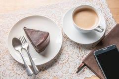 Διάλειμμα με το κέικ σοκολάτας στον πίνακα Στοκ Φωτογραφίες