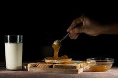 Διάδοση της μαρμελάδας στις φέτες του ψωμιού με το γάλα στο μαύρο υπόβαθρο Στοκ Φωτογραφίες