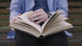 Διαβάζοντας σε ένα βιβλίο και στα κτυπήματα μια σελίδα κοντά επάνω απόθεμα βίντεο