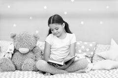 Διαβάστε πριν από τον ύπνο Το παιδί κοριτσιών κάθεται το κρεβάτι με το teddy διαβασμένο αρκούδα βιβλίο Το παιδί προετοιμάζεται να στοκ φωτογραφία με δικαίωμα ελεύθερης χρήσης