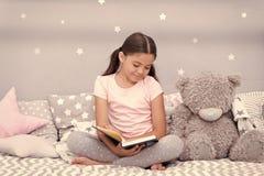 Διαβάστε πριν από τον ύπνο Το παιδί κοριτσιών κάθεται το κρεβάτι με το teddy διαβασμένο αρκούδα βιβλίο Το παιδί προετοιμάζεται να στοκ φωτογραφίες