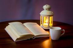 Διαβάστε το βιβλίο λαμβάνοντας υπόψη ένα φανάρι με ένα φλιτζάνι του καφέ ή ένα tea_ στοκ φωτογραφία με δικαίωμα ελεύθερης χρήσης