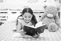 Διαβάστε το παραμύθι στο κρεβάτι Το παιδί κοριτσιών βάζει το κρεβάτι με το teddy διαβασμένο αρκούδα βιβλίο Το παιδί προετοιμάζετα στοκ εικόνες