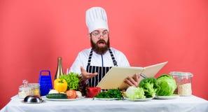 Διαβασμένες μάγειρας συνταγές βιβλίων Το άτομο μαθαίνει τη συνταγή Δοκιμάστε κάτι νέο Μαγειρική στο μυαλό μου Ικανότητα μαγειρέμα στοκ φωτογραφίες