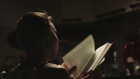 Διαβασμένο γυναίκα βιβλίο στην κουζίνα απόθεμα βίντεο
