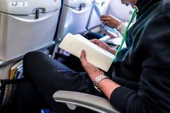 διαβασμένο επιβάτης βιβλίο συμμετοχής στο κάθισμα αεροπλάνων στοκ εικόνες