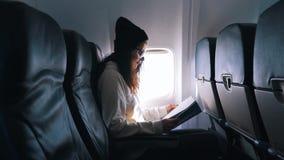 Διαβασμένο κορίτσι βιβλίο κατά τη διάρκεια της πτήσης φιλμ μικρού μήκους