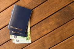Διαβατήρια με τα ευρο- τραπεζογραμμάτια σε έναν ξύλινο πίνακα Readine ταξιδιού στοκ εικόνες