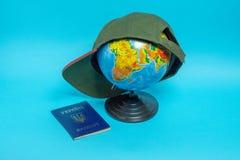 Διαβατήριο ενός πολίτη της Ουκρανίας κοντά στη σφαίρα με ένα καπέλο του μπέιζμπολ στοκ εικόνες