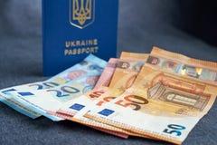 Διαβατήριο της Ουκρανίας με ευρο- Bill μέσα Σε ένα γκρίζο backgraund Στοκ Εικόνες