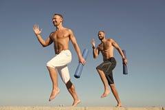 Διαβιβάστε στον υγιή τρόπο ζωής Τα άτομα με το χαλί γιόγκας συνέλαβαν στο υπόβαθρο μπλε ουρανού κινήσεων Αθλητικός τύπος με το τρ στοκ φωτογραφία με δικαίωμα ελεύθερης χρήσης