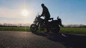 Διαβιβάστε στο όνειρο και το ταξίδι Ο ποδηλάτης με το κράνος στο χέρι του πηγαίνει στη μοτοσικλέτα απόθεμα βίντεο