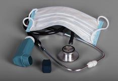 Διαγνωστικό εργαλείο - phonendoscope, επίδεσμος γάζας, inhaler με το διανομέα, σε γκρίζο Στοκ Εικόνες